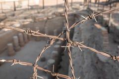 Unclearly schilderde kolommen van een opgegraven tempel dichtbij Kerma in de Soedan achter scherp geconcentreerd prikkeldraad, Af stock foto