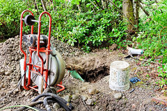 Unclogging drainage pipes. Removing tree roots from groundwater drainage pipe in a back yard stock photos