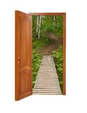 Unclosed wooden door with a kind on a wooden path in a birchwood Stock Photo