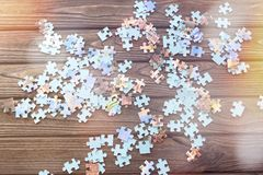 Uncollected group of puzzles on a wooden table background. Preschool education Stock Photo