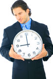 Uncomfortable Businessman Holding Clock Royalty Free Stock Images