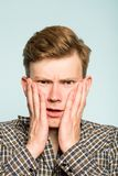 Uncomprehending puzzled confused man disbelief. Uncomprehending puzzled perplexed confused man grasping his face in disbelief. portrait of a young guy on light stock photography