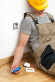 Unconcious electrician. Electrician paralysed by electricity during repairing a socket stock photo