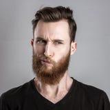 Unconfident και ανησυχημένος νεαρός άνδρας που απομονώνονται στο γκρίζο υπόβαθρο Στοκ Εικόνα