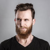 Unconfident και ανησυχημένος νεαρός άνδρας που απομονώνονται στο γκρίζο υπόβαθρο Στοκ Εικόνες