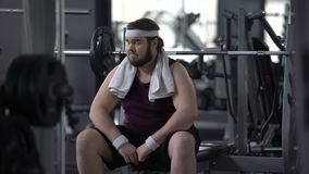 Unconfident chubby man in gym feeling upset because of excess weight, shyness stock footage
