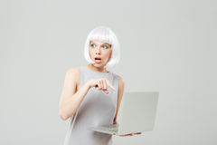 Unconfident pretty young woman holding and using laptop Royalty Free Stock Photos