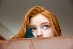 Unconfident shy redhead girl peeping from sofa Royalty Free Stock Photography