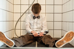 Unconscious boy holding running shower head Stock Images