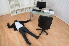 Unconscious Businessman Lying On Floor. Unconscious Young African Businessman Lying On Floor In Office Stock Photo