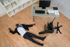 Unconscious Businessman Lying On Floor. Unconscious Young African Businessman Lying On Floor In Office Royalty Free Stock Image