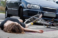 Unconscious cyclist after road accident. Unconscious female cyclist lying on street after road accident Stock Photography