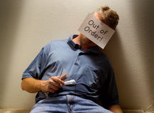 Unconscious drunk man with Out of Order sign. Unconscious alcoholic drunk man passed out with his drink spilled all over him with an Out of Order sign Royalty Free Stock Photo