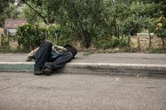 Unconscious drunk man outdoors. Person lying on the pavement Stock Image