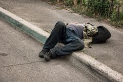 Unconscious drunk man. Person lying in the street. Health problems of the homeless Stock Image