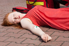 Unconscious girl with intravenous cannula. In her arm Stock Images