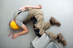 Unconscious handyman on the floor. Handyman lying unconscious on the floor near the ladder Royalty Free Stock Images