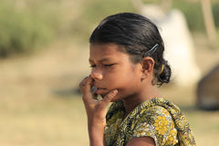 Unconscious India girl is cleaning nose. Stock Photos