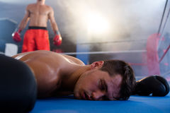 Unconscious male boxer lying by athlete in ring. Unconscious male boxer lying by athlete in boxing ring at fitness studio royalty free stock photography
