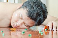 Unconscious man with pill on hand. Unconscious man with bottle of pill in hand Stock Images