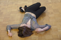 Unconscious woman on the ground. Unconscious woman lying on the hardwood  flooring Stock Images