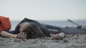 Unconscious woman lying on seashore, drowned swimmer, victim of shipwreck. Stock footage stock video footage