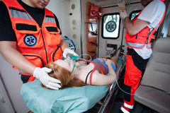 Unconscious woman and working paramedics. Unconscious women and working paramedics in ambulance Royalty Free Stock Images