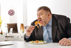 Uncontrolled excessive employee dreaming about some sweets. Wish you were here. Overweight weak willed unhealthy guy sticking to his new diet but thinking about Royalty Free Stock Photos