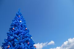 Unconventional blue christmas tree. With blue sky background, blue color concept, christmas in the tropics Royalty Free Stock Photo