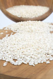 Uncooked arborio rice. Risotto arborio white rice in a bowl over wooden board Royalty Free Stock Image