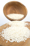 Uncooked arborio rice. Risotto arborio white rice in a bowl over wooden board Royalty Free Stock Photography