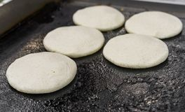 Uncooked arepas, traditional Venezuelan corn patties, at a street food market.