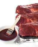 Uncooked Baby Back Ribs With BBQ Sauce. Vertical of raw beef ribs setting in a broiling pan with foil lining on white background with a bowl of BBQ sauce and royalty free stock photography