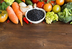 Uncooked black lentils in a bowl with vegetables Stock Photos