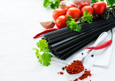 Uncooked black pasta with tomatoes, fresh herbs and spices Royalty Free Stock Photography