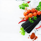 Uncooked black pasta with tomatoes, herbs, spices  Royalty Free Stock Images