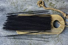 Uncooked black spaghetti. High angle view of a bunch of uncooked black spaghetti on a wooden chopping board, placed on a gray rustic wooden table Royalty Free Stock Image