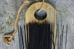 Uncooked black spaghetti. A pile of uncooked black spaghetti on a wooden chopping board, placed on a gray rustic wooden table Stock Images