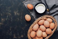 Uncooked brown eggs in a basket and milk in a jug on a dark rustic background. Top view, copy space.