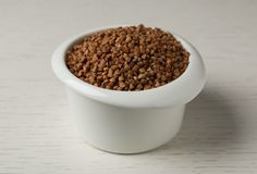 Uncooked buckwheat in ceramic bowl. On table royalty free stock photo