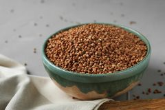 Uncooked buckwheat in ceramic bowl. On table stock photography