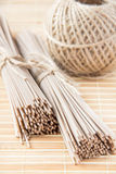 Uncooked buckwheat noodles on bamboo table Royalty Free Stock Photo
