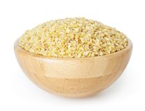 Uncooked bulgur in wooden bowl isolated on white Stock Photo