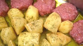 Uncooked burgers and potatoes with oregano and sauce in fresh greek olive oil. Close up of uncooked burgers and potatoes with oregano and sauce in fresh greek stock video