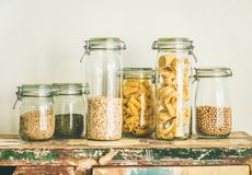 Uncooked cereals, grains, beans and pasta in jars on table. Various uncooked cereals, grains, beans and pasta for healthy cooking in glass jars on rustic table Royalty Free Stock Photo