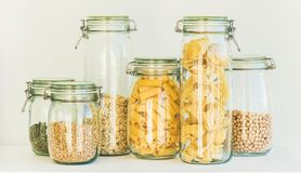 Uncooked cereals, grains, beans and pasta in jars. Various uncooked cereals, grains, beans and pasta for healthy cooking in glass jars on kitchen shelf, white Stock Photos