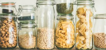 Uncooked cereals, grains, beans and pasta on rustic table, close-up. Various uncooked cereals, grains, beans and pasta for healthy cooking in glass jars on Royalty Free Stock Photos