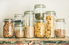 Uncooked cereals, grains, beans and pasta on rustic table. Various uncooked cereals, grains, beans and pasta for healthy cooking in glass jars on wooden table Stock Images