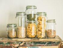 Uncooked cereals, grains, beans and pasta on rustic wooden table. Various uncooked cereals, grains, beans and pasta for healthy cooking in glass jars on rustic Royalty Free Stock Photos