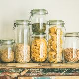 Uncooked cereals, grains, beans and pasta on table, square crop. Various uncooked cereals, grains, beans and pasta for healthy cooking in glass jars on wooden Royalty Free Stock Image